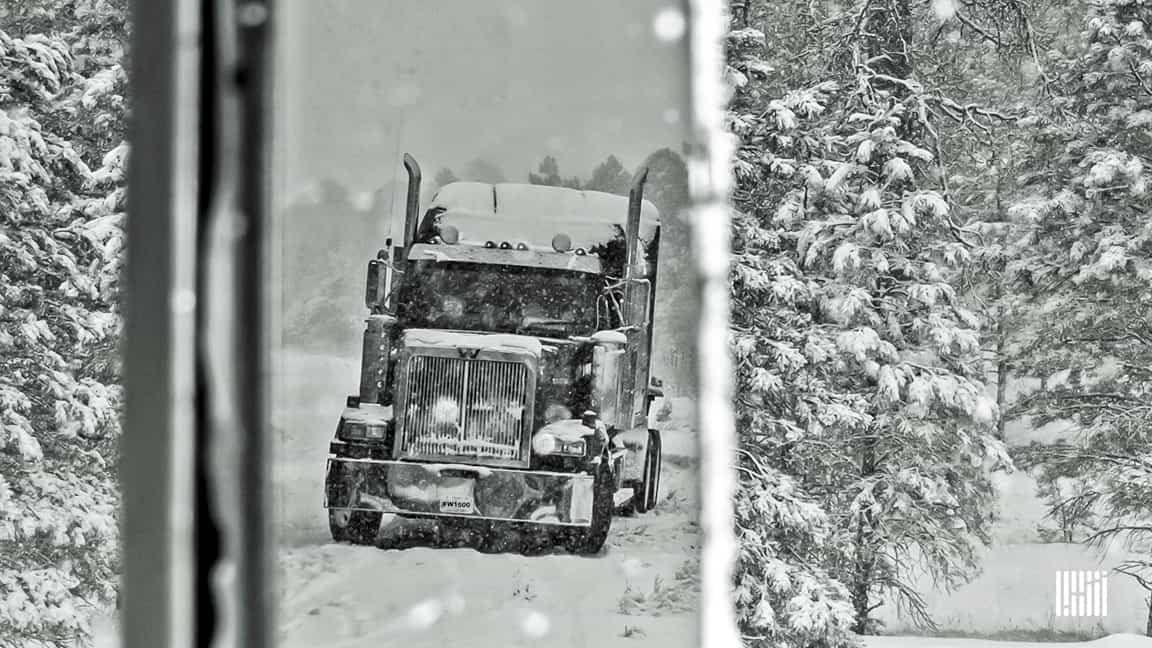 Tractor-trailer heading down snowy highway.