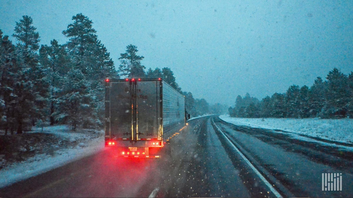 Tractor-trailer heading down wet road with snow on the shoulders and grassy areas.