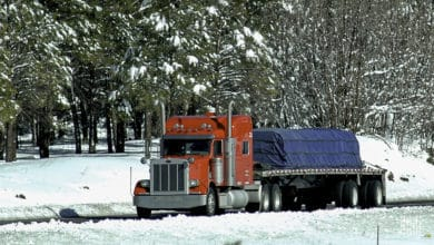 Flatbed tractor-trailer heading down a snowy road.