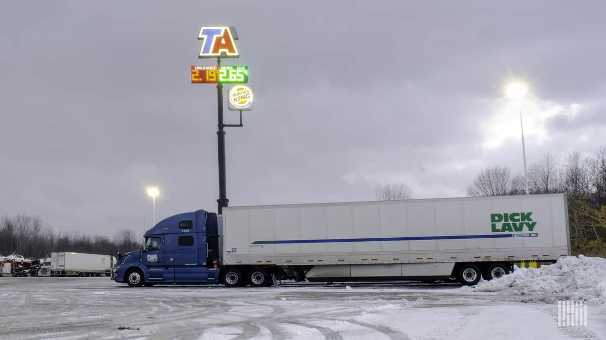 Driver entering truck stop on a snowy day.