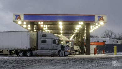 Drivers at a truck stop on a snowy day.