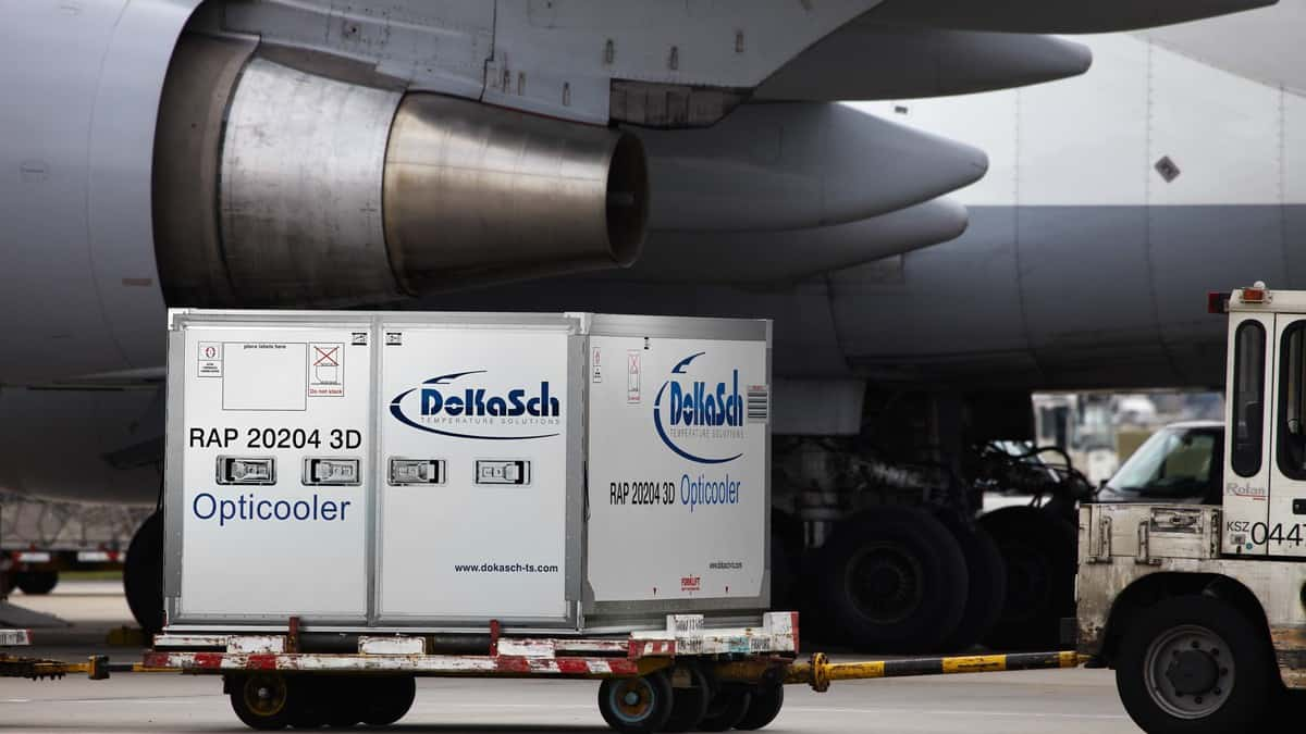 A large cooler on wheels for medicine transport sits on tarmac beneath an airplane wing. Air transport is commonly used to ship medicines.