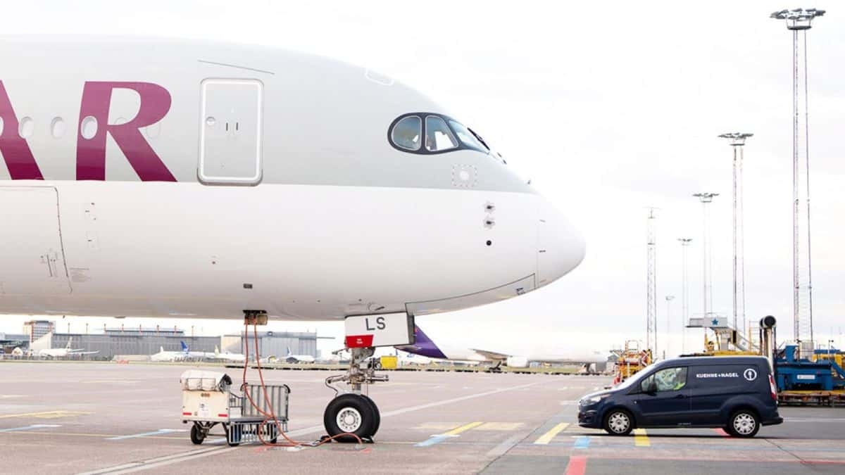 The front end, nose of a a grey plane with white underbelly, shot from the side with a blue van parked facing the plane after arriving at airport.