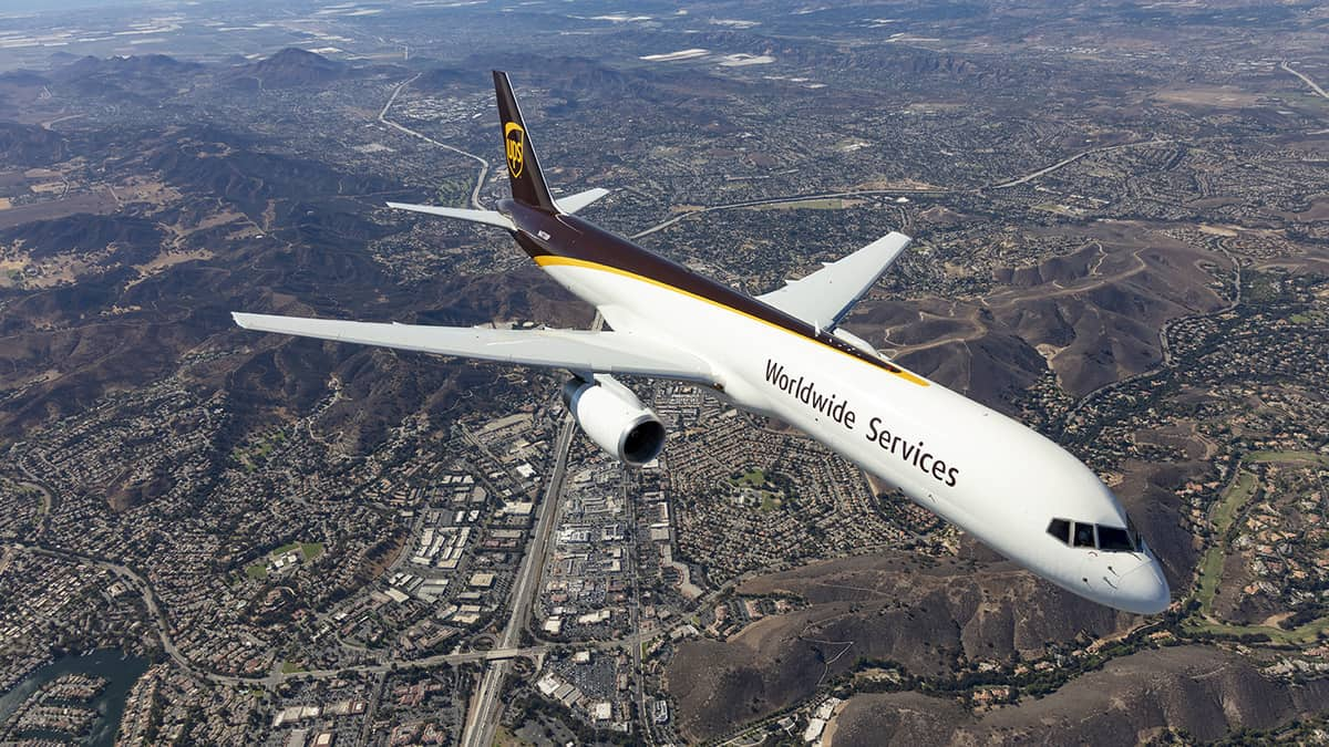 A white UPS cargo jet with brown tail flies over populated area. View is looking down from above aircraft.