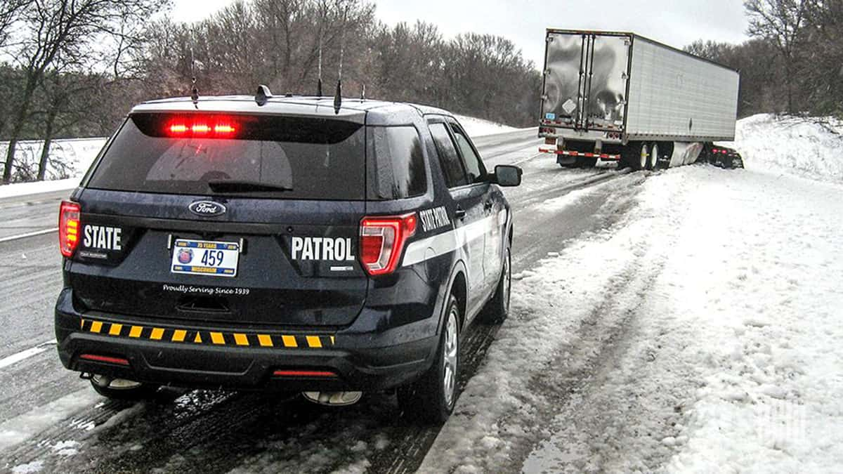 Law enforcement on scene of tractor-trailer accident on snow Wisconsin road.