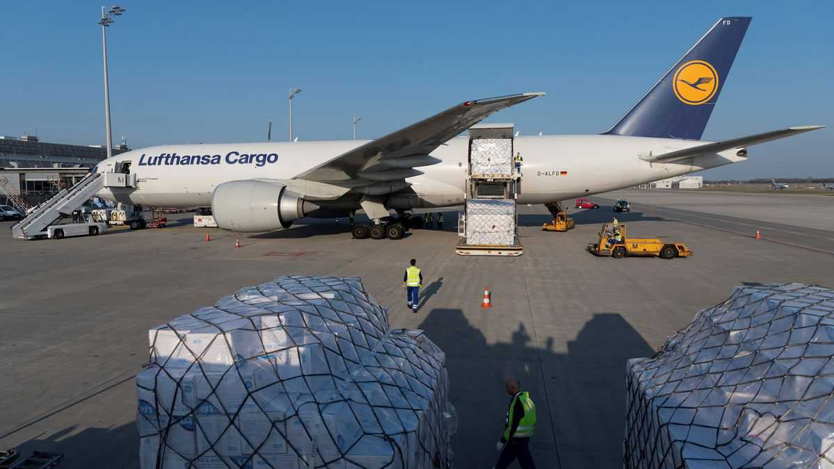 A white Lufthansa plane with blue tail and cargo pallet sitting on ground.