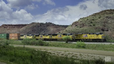 A photograph of a Union Pacific train hauling intermodal containers across a desert.