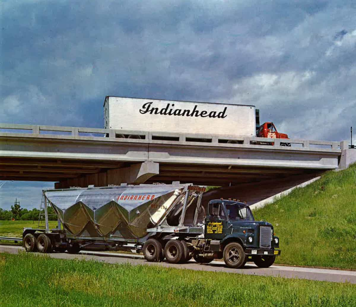 An Indianhead tractor-trailer passes above an Indianhead tanker.