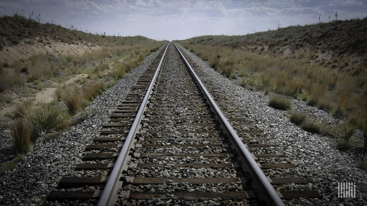 A photograph of a railroad track in a field.