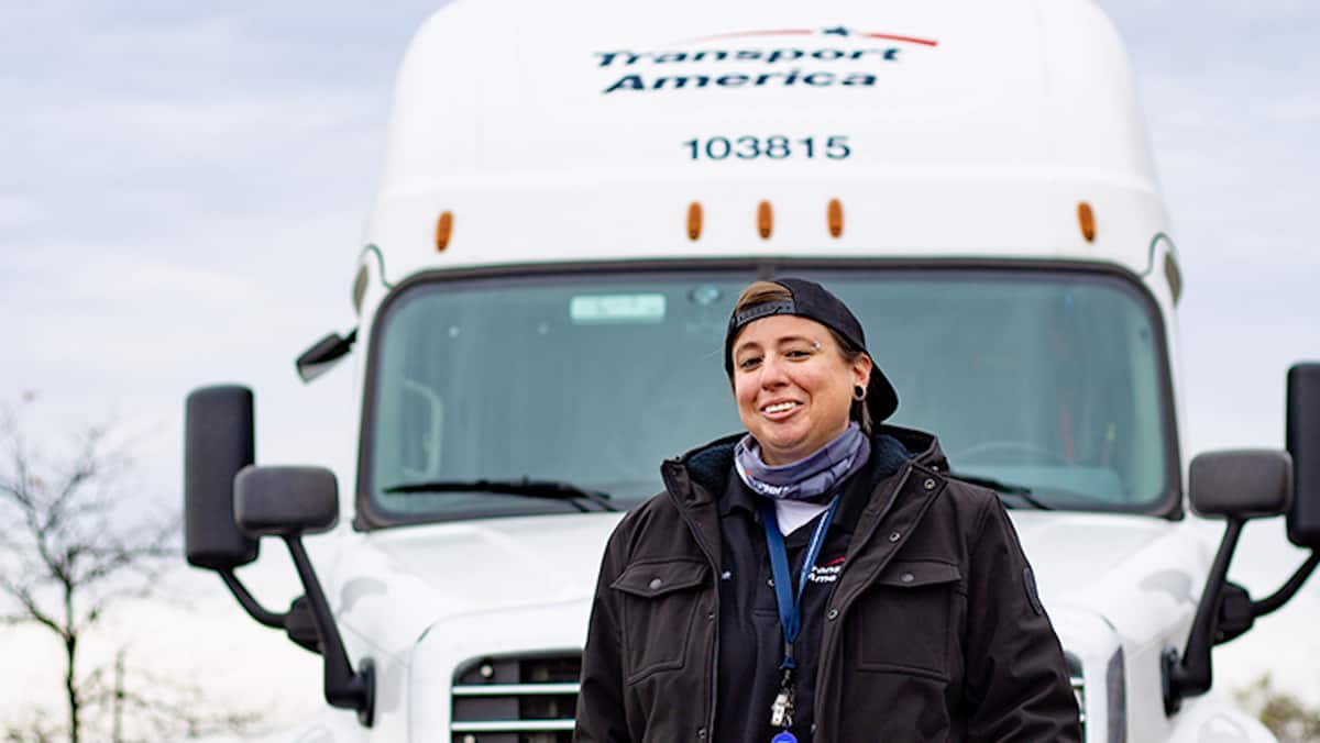 A Transport America driver in front of a tractor-trailer. The carrier has been shifting drivers to dedicated trucking services.