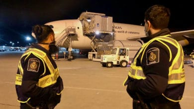 Two Canada Border Services officers watch COVID-19 vaccines get unloaded from a UPS plane that delivered Canada's first shipments.