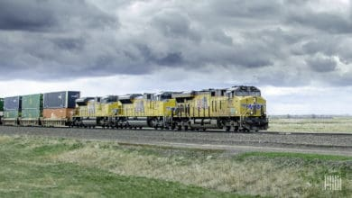 A photograph of a Union Pacific train hauling intermodal containers across a field.