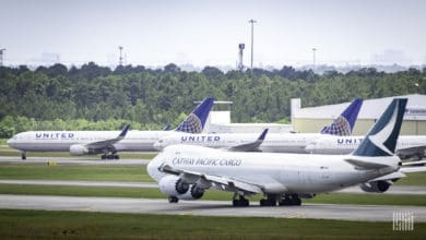 A white jumbo jet begins to move down runway with parked planes in the background.