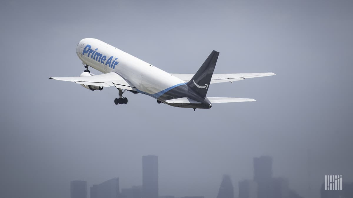 A white Amazon Air jet with blue tail lifts off with city skyline in background.