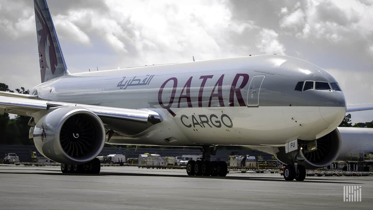 A Qatar Airways Cargo jet, beige on top and white on bottom parked on a sunny day.