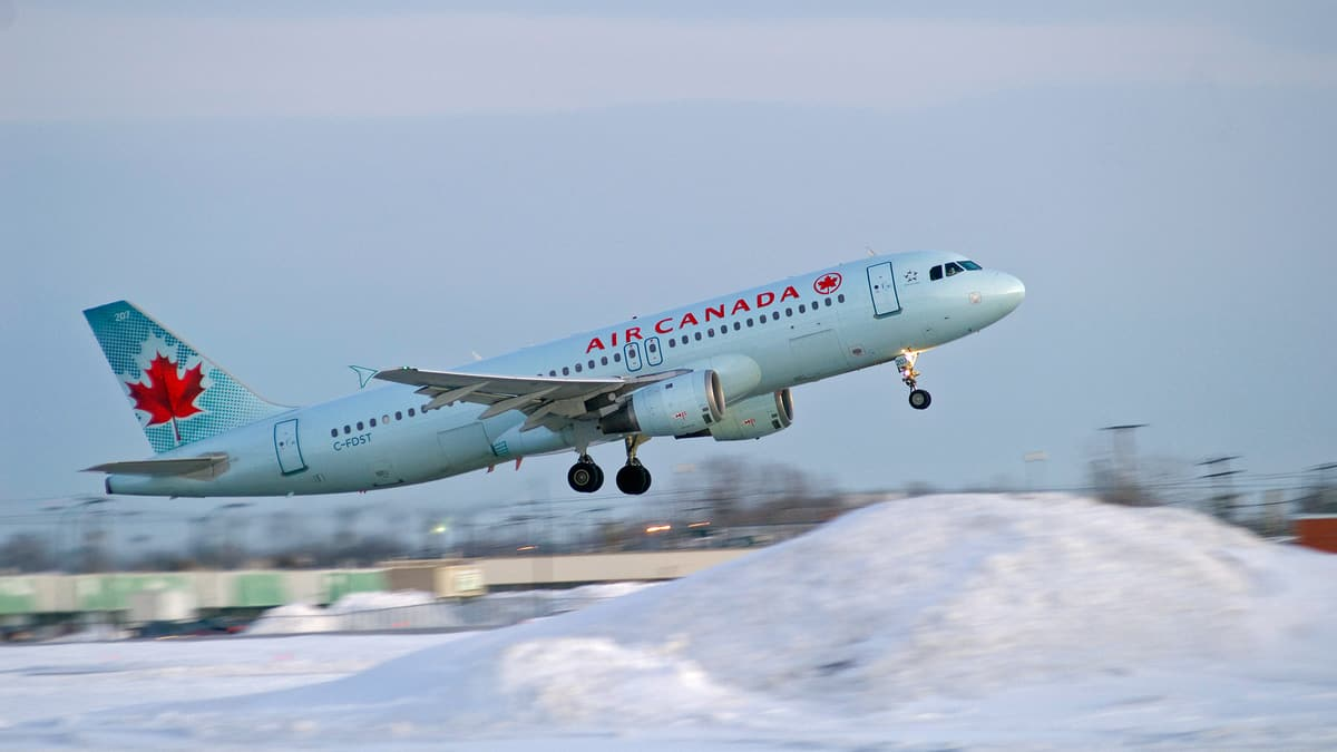A gray/white Air Canada jet takes off on an overcast day with snow in the foreground.