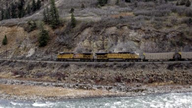 A photograph of a Union Pacific train traveling by a rocky mountainside.