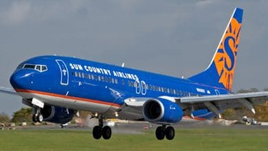 A bright blue Boeing 737 with orange lettering lands on runway.