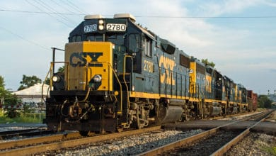 A CSX train travels down train track.