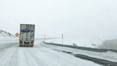 Swift tractor-trailer heading down snowy California highway.
