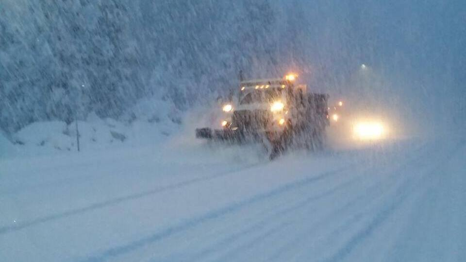 Plow truck trying to clear a snowy California highway. during a blizzard