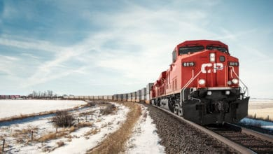 A photograph of a Canadian Pacific train traveling through a snowy field.