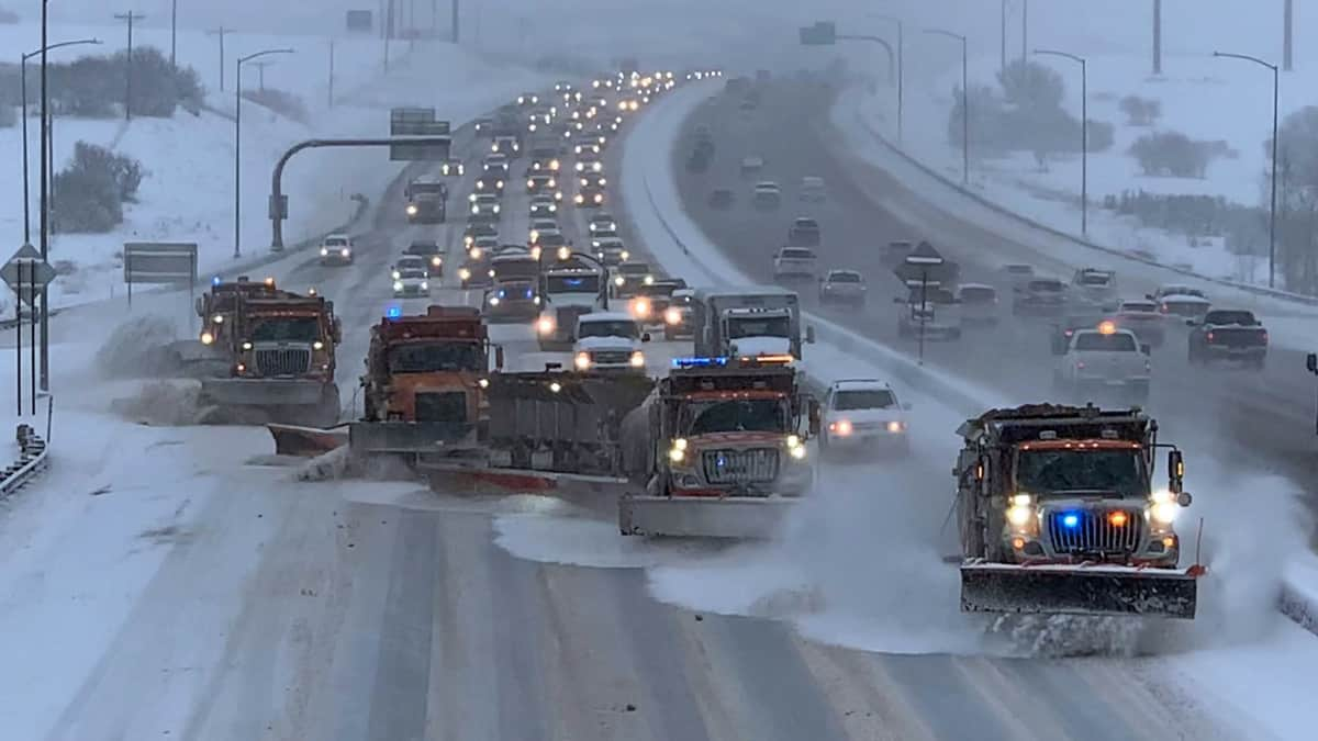 Traffic buildup behind several plows clearing a Colorado highway.