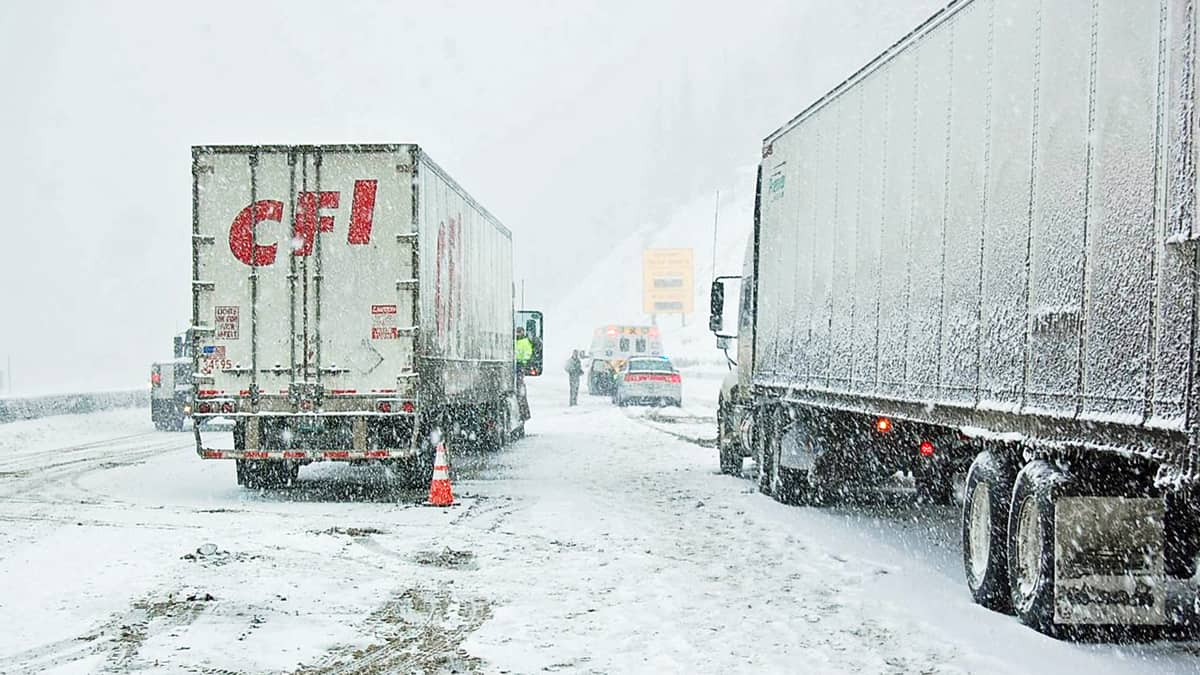 Tractor-trailers stopped on a snowy Colorado highway.