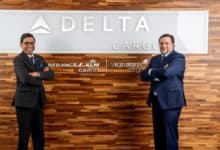 Delta Cargo executives standing in front of company sign at office.