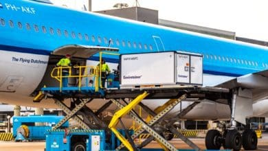 A temperature-controlled container on a lift gets loaded in side of a light blue plane.