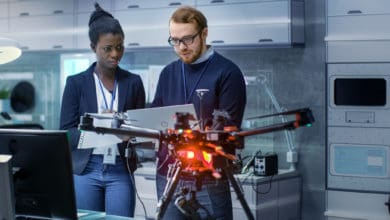 Two people look at a document with a drone positioned in the foreground.