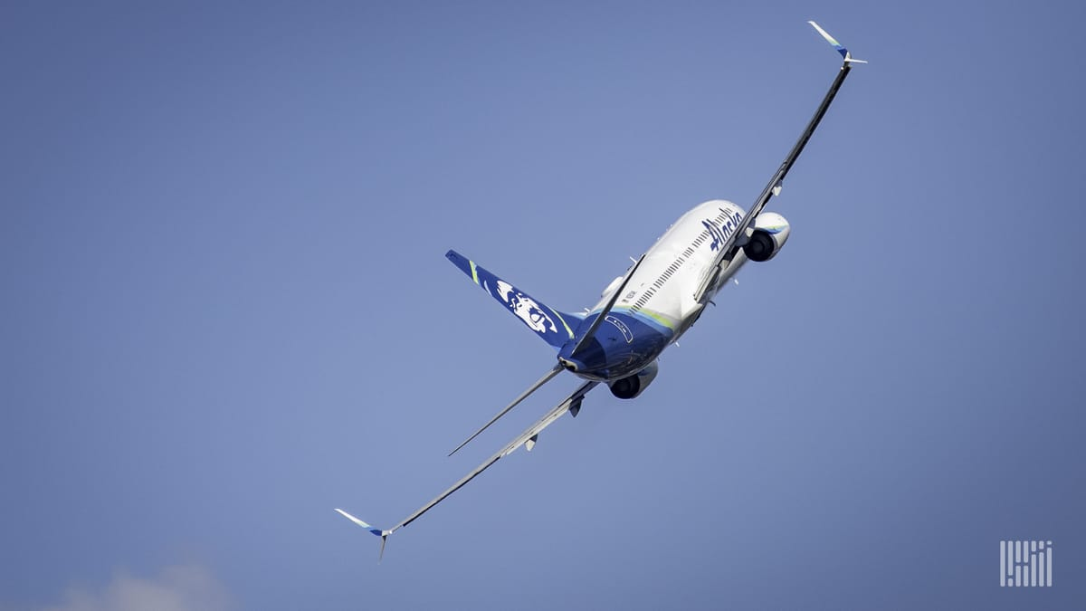 A white Alaska Airlines jet banks to the left during its climb into a blue sky, view from behind.