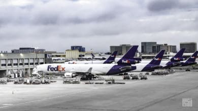 FedEx aircraft, white with blue tails, parked at airport.