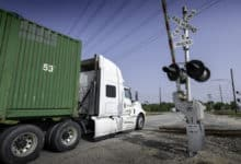 A photograph of a truck at a railroad crossing.