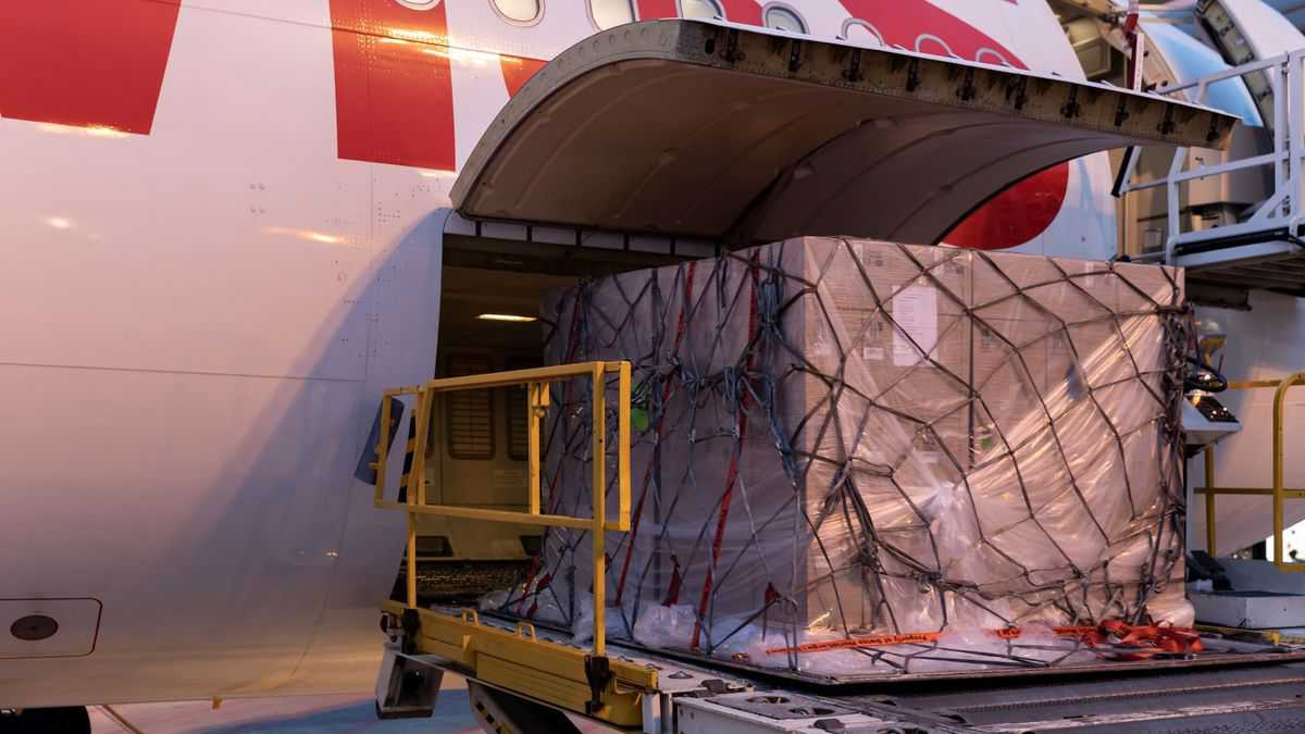 A large pallet of cargo on a hydraulic lift gets loaded into the side door of a plane.