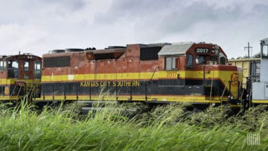 A photograph of a Kansas City Southern train traveling through a grassy field.
