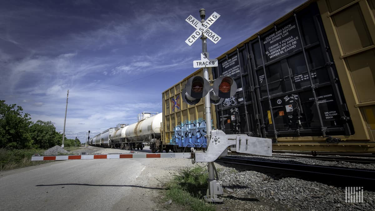 A photograph of a train passing by a railroad crossing.