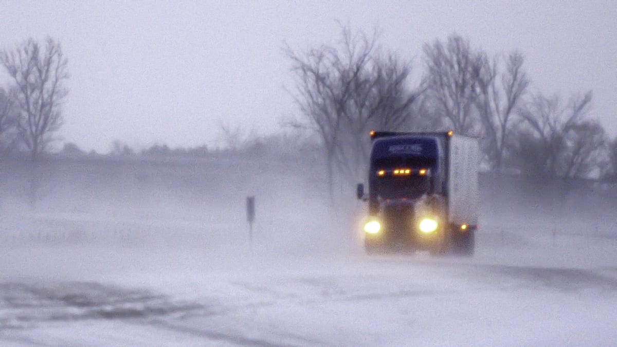 Tractor-trailer moving through a Minnesota blizzard.