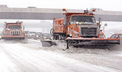 Plow trucks clearing a Minnesota highway, with traffic behind it.