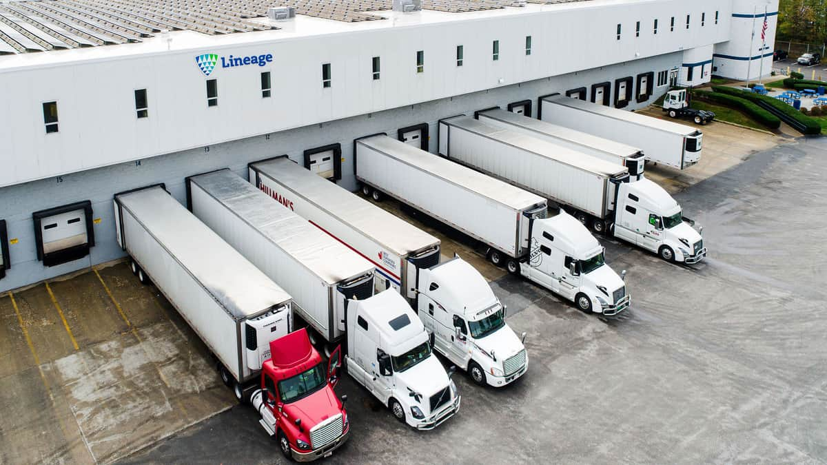 A photograph of a warehouse with five trucks parked next to it.
