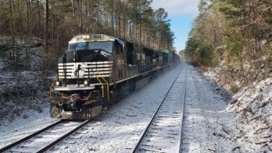 A photograph of a Norfolk Southern train traveling through the snow.