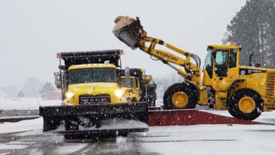 Plow trucks clearing a snowy North Carolina highway.