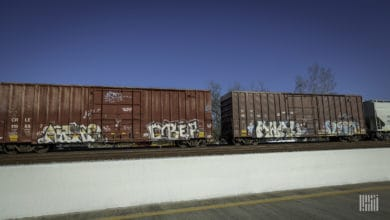 A photograph of boxcars in a rail yard.