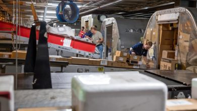 Workers at an express air hub as packages come down chutes into air cargo containers.