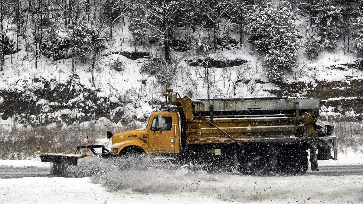 Plow truck clearing snow covered mountain highway.