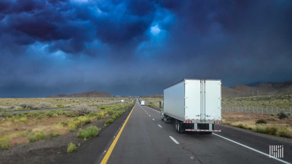 Tractor-trailer heading down highway with thunderstorm cloud across the sky.