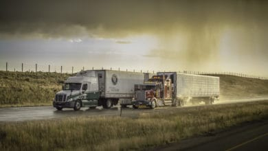Tractor-trailers heading down highway with storm cloud on the horizon.