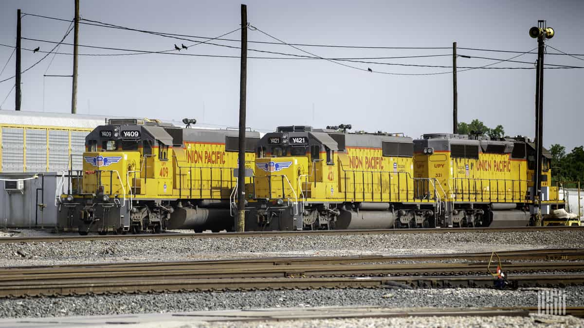 A photograph of three Union Pacific locomotives in a rail yard.