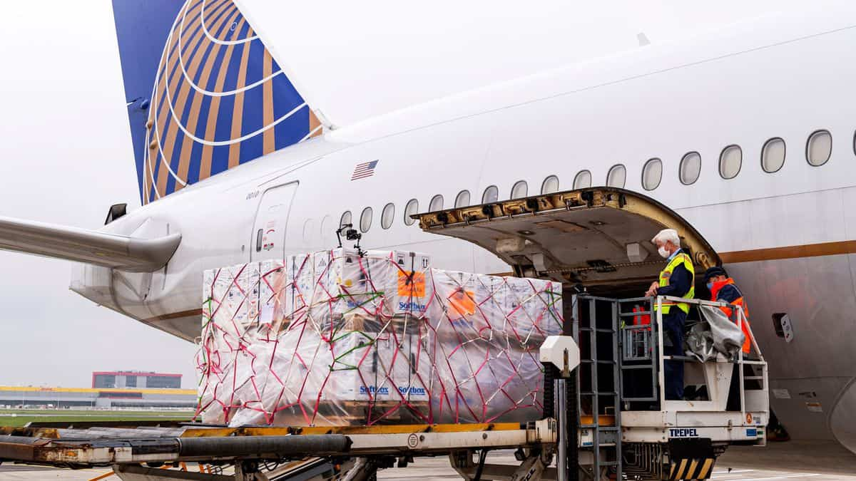 Plastic wrapped pallets of cargo loaded in side door of white United jet, with blue tail.