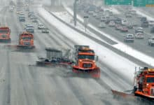Traffic behind plow trucks clearing Utah highway.